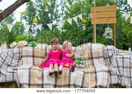 Two children in a pink dress sitting on the couch with makeshift equipment
