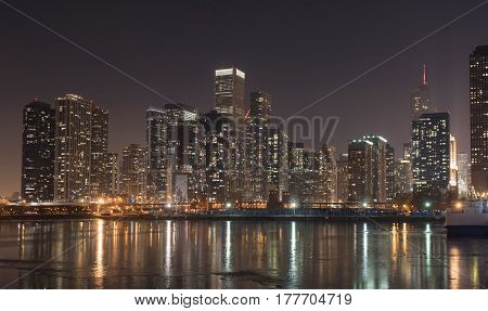 Side view of frozen lake reflecting lanterns of Chicago downtown. Panorama concept