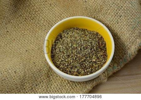 Marjoram leaves herb is small spice dish on burlap