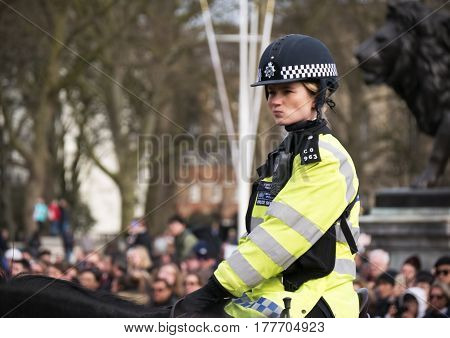 LONDON - 2017 March 17 United Kingdom : Metro cop leads traffic from horseback at Buckingham Palace in London. Police on horseback in the UK for the prevention of crime.
