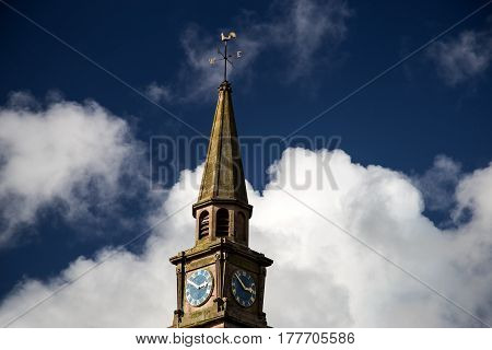 Church steeple and clock against a blue sky with white clouds