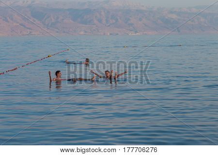 Couple Floating And Having Fun In The Dead Sea. The Lowest Elevation On Earth.