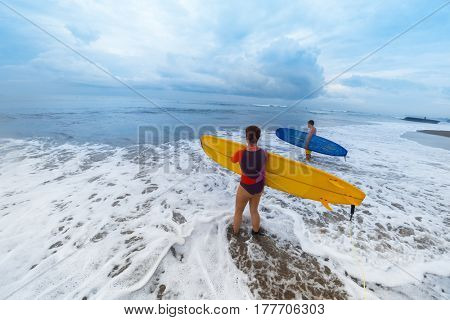 Two surfers coming into the ocean with surf boards