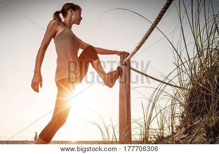 Woman performs stretching exercises on a beach at sunrise