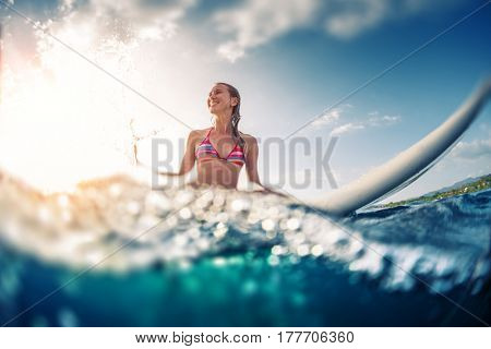 Happy smiling woman sits on the surfboard in the ocean. Tilt shift effect, image has blurred edges.