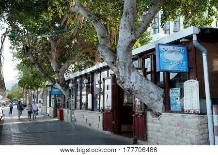 TIBERIAS ISRAEL - FEBRUARY 26 2017: Restaurant on the promenade in Tiberias. Trunks of trees grow through the wall of the restaurant
