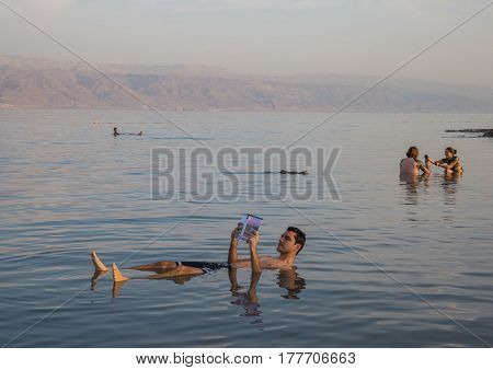 KALIA BEACH DEAD SEA ISRAEL - FEBRUARY 27 2017: Man reads book floating on dead sea and couple applies mud treatment on body.
