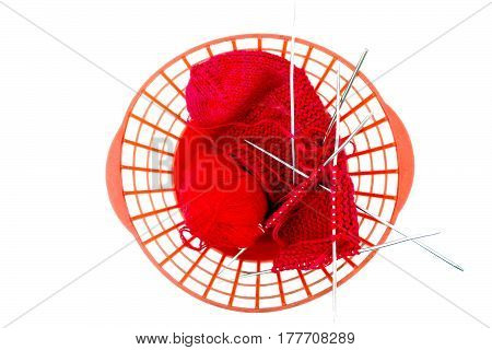 Knitting needles, a red woolen thread in a tangle and needlework on white background. Wool yarn