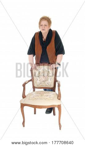 A senior woman in her seventies standing behind a old armchair looking serious isolated for white background.