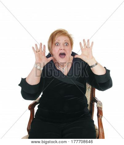 A scared looking senior woman sitting in an old armchair hands up and screaming with mouths open isolated for white background.