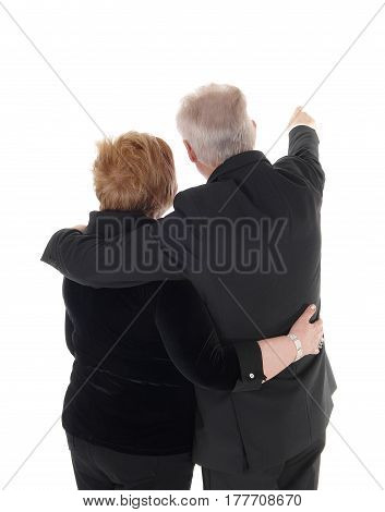 A senior citizen couple standing from the back and waist up pointing with one hand isolated for white background.