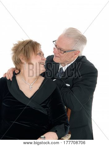 A very happy senior citizen couple looking smiling at each other in love isolated for white background.