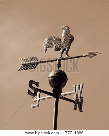 very old weathervane with sepia effect with arrow