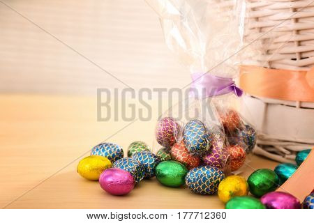 Chocolate eggs in colorful foil near traditional Easter basket on light wooden table