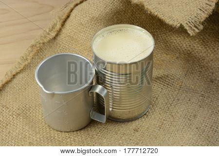 Canned evaporated milk and vintage retro measuring cup on burlap