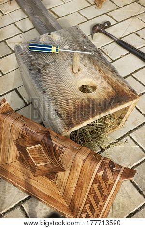 Old Birdhouse Repair In Spring, Cap Is Covered With Linoleum