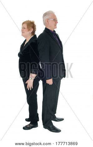 A gorgeous and handsome senior couple standing in a suit back to back isolated for white background.