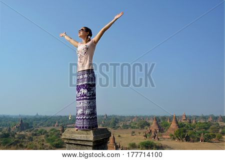 Young woman with wide spread hands facing the sun. Bagan temples at the background. Freedom joy and happiness.
