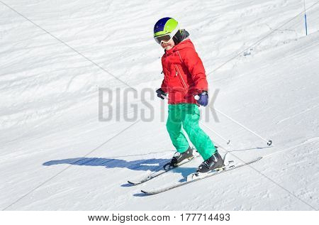 Little skier learning and exercising in winter school in alpine resort