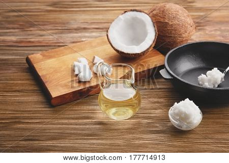 Glass jug with coconut oil and kitchenware on wooden background