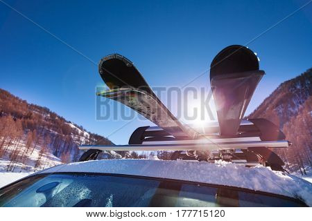 Car roof with two pairs of skis on the rack at sunny winter day