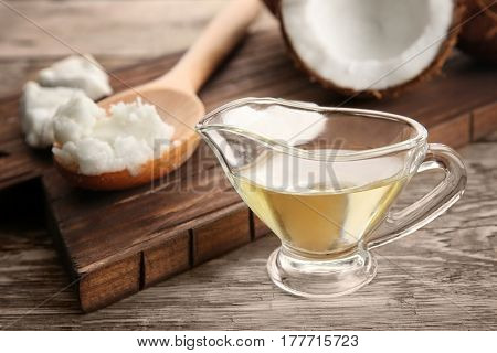 Coconut and kitchenware with fresh oil on wooden board