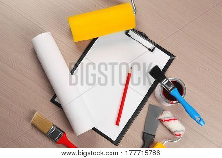 Clipboard and decorator instruments on wooden table