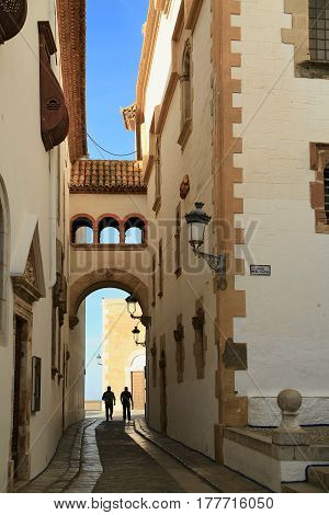 People walking a narrow street between the Museum Maricel de Mar and Palace Maricel at sunrise in town of Sitges. Catalonia, Spain.