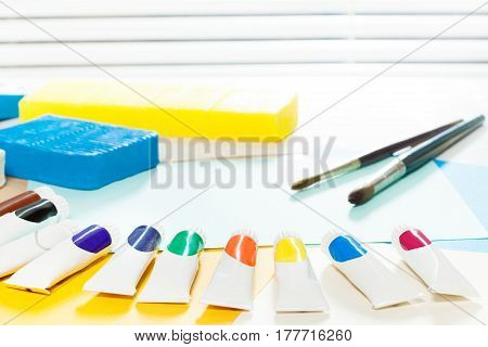 Sheet of blue paper, brushes, multicolored paints and modeling clay laying on the table during visual art lesson