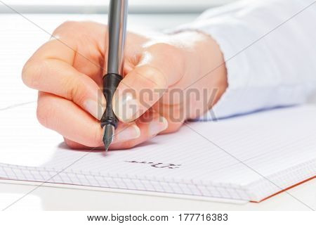 Close-up picture of woman's hand making notes on the ring-bound notebook with metallic fountain pen at the table