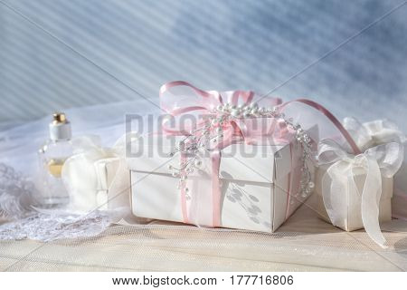 Wonderful composition of gift boxes, perfume and bridal veil on light background