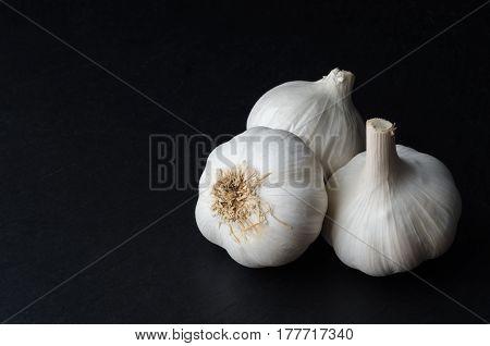 Three Whole Garlic Bulbs On Black
