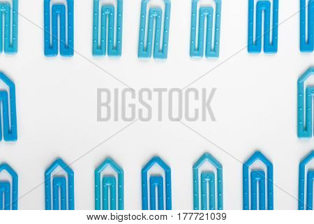 many blue paper clip on a white paper sheet with space for text