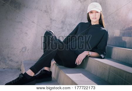 Athletic sporty young woman sitting down on steps