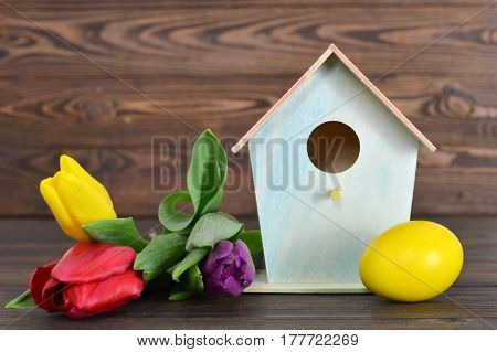 Happy Easter: Easter egg birdhouse and spring flowers