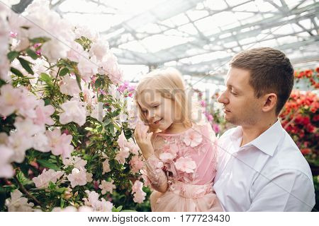 A young father holding a small daughter in his arms who admires flowers in a spring flowering garden