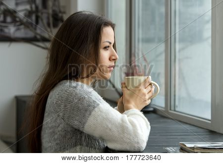 A girl in a bright sweater holding a cup near the lips and looking into the distance through the window leaning on the wooden sill.