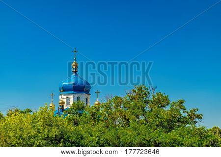 The reflection of the sun in the dome of the Rural Christian Church in Ukraine. Landscape with the domes of the Church peeking through the trees of the forest