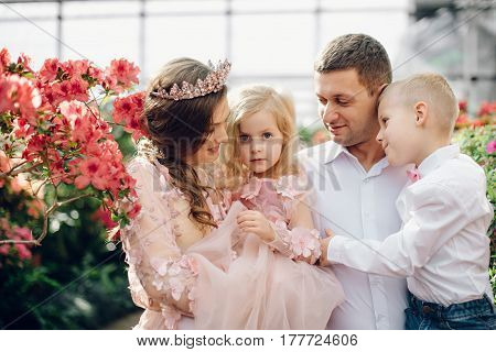 Young happy family - mom dad daughter and son in a blooming spring garden close-up