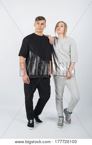 Fashion girl leans on boy's shoulder. Young muscular man wearing black clothes and sneakers with girl in grey clothes solated on white background