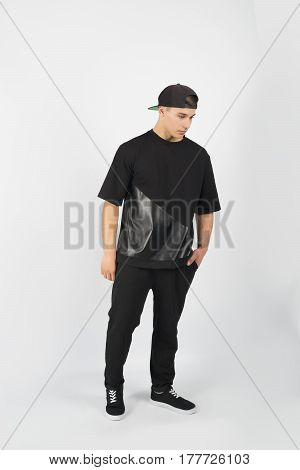 Young muscular man wearing black clothes and snapback with sneakers isolated on white background