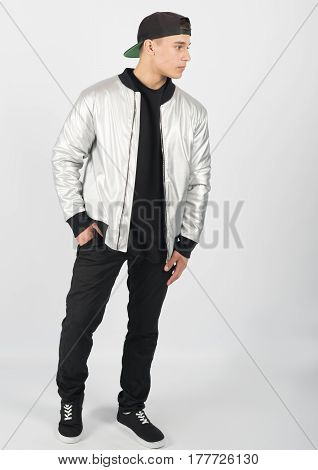 Young muscular man wearing black trousers grey jacket snapback and sneakers on white background