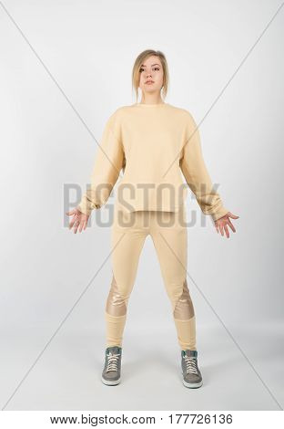 Young beautiful girl wearing yellow clothes and sneakers posing on white background. hands down in opposite directions