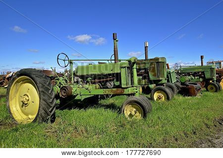 BARNESVILLE, MINNESOTA- September 26, 2016; A row of old green tractors left in the long grass are producst of John Deere Co, an American corporation that manufactures agricultural, construction, forestry machinery, diesel engines, and drive trains