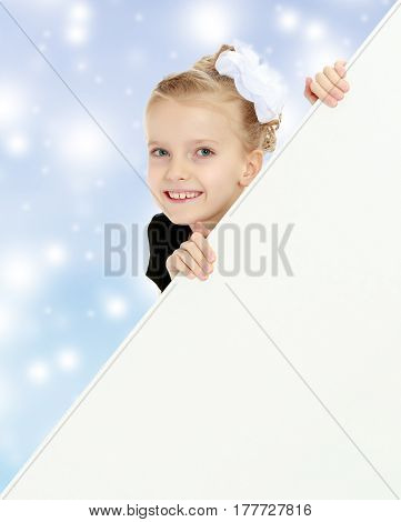 Beautiful little blonde girl dressed in a white short dress with black sleeves and a black belt.The girl peeks out from behind white banner.Close-up.Blue Christmas festive background.