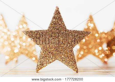 Macro made of textured glittering golden star on festive background.