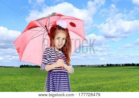 Beautiful little girl long hair and white bow on her head , in a summer dress in stripes.She stands under the umbrella.On the background of green grass and blue sky with clouds.