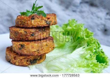 Fried vegetable patties on a plate. Yummy patties made of potatoes, green peas, carrot and green beans and garnished with fresh green onion. Veggie lunch or dinner idea. Vintage style. Closeup