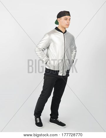 Young muscular man wearing black trousers grey jacket and sneakers on white background