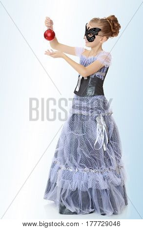 Slender little girl , with beautiful hair on his head, elegant long Princess dress.Posing in carnival mask.She admires the beautiful Christmas decorations.On the pale blue background.